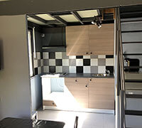 La cuisine du lodge confort PMR en location, au camping l'Ecrin vert proche de Rodez